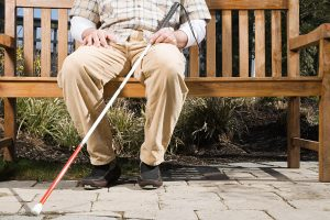 Picture of blind person with cane sitting on a bench